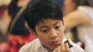 Happy asian boy eating japanese food. video