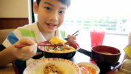 Happy asian boy eating japanese lunch set video