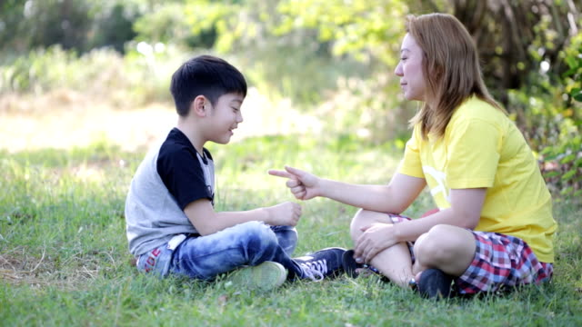 Happy asian child and mother playing in the park video