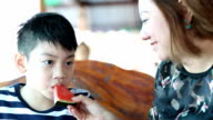 Happy Asian child with mother enjoy eating ripe watermelon . video