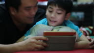 Happy asian family Father and son looking on tablet screen, in the bedroom video