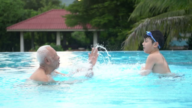 Happy asian family playing in pool, Asian grandchildren and grand parents swimming in pool. video