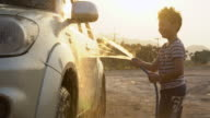 Happy asian kid washing car with water spray .4K shoot with sunset and flare Shoot By Sony A6300 video