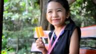 Happy Asian little girl with orange   ice cream video
