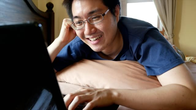 happy asian man using laptop computer for chat online messaging on bed video