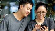 Happy asian man with girl friend using cell phone video