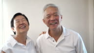 Happy Asian senior couple on white background. Laughing and talking video