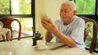 Happy asian senior man using the mobile phone at home video
