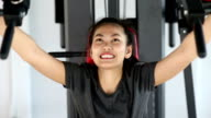 Happy asian young woman exercising on shoulder press in fitness center video