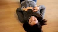 Happy asian young woman lying using smart phone at home video
