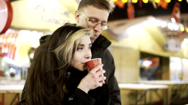 Happy attractive couple drinking tea in a christmas market at night. Beautiful lights background. video