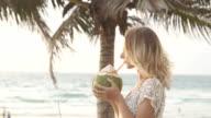 Happy beach bikini woman relaxing drinking fresh coconut water lying down sunbathing on fun Caribbean vacation video