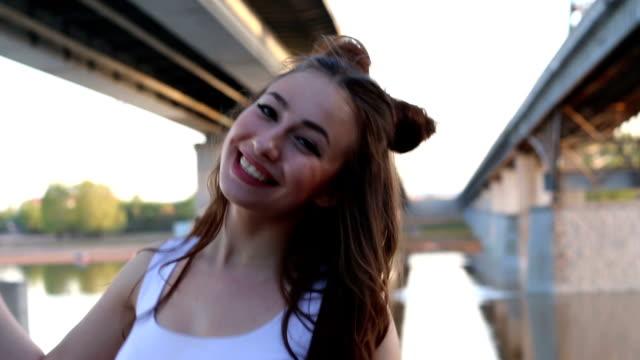Happy beautiful girl dancing on background of bridge video