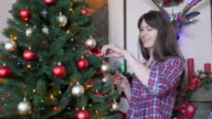 Happy beautiful woman decorates a Christmas tree video