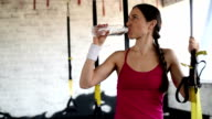 happy beautiful woman  drinks water. TRX straps. video