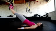 happy beautiful woman is  lying with the TRX straps. video