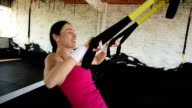 happy beautiful woman is  training with the TRX straps. video