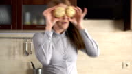 Happy beautiful young businesswoman having silly fun in kitchen in the morning, dancing with cookies video
