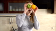Happy beautiful young businesswoman having silly fun in kitchen in the morning, dancing with fruits video