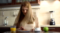 Happy beautiful young woman having silly fun in kitchen in the morning, singing and playing music video