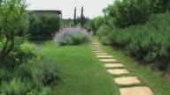 Happy blond woman walking in marvelous flowered Tuscan garden. video