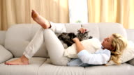Happy blonde petting her grey fluffy cat on the couch video