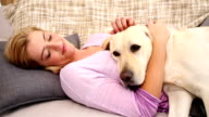 Happy blonde petting labrador on couch video