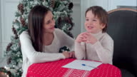 A happy boy and his mother fantasizing what to write in a letter to Santa video