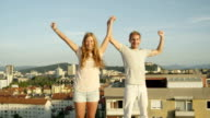 CLOSE UP: Happy boy and smiling girl standing on rooftop raising hands in sky video