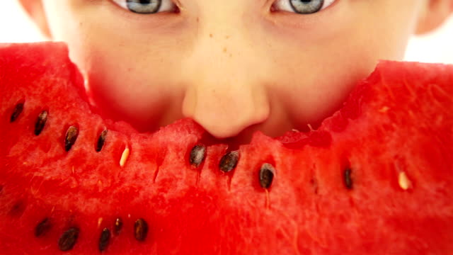 Happy boy appetizing eating red watermelon and juice flowing under the teeth video