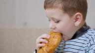 happy boy eating croissant and thumb up video