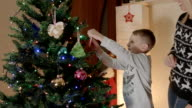 happy boy hanging gingerbread on christmas tree with mother video