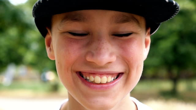 A happy boy in a cap smiles while standing in a picturesque park in slo-mo video