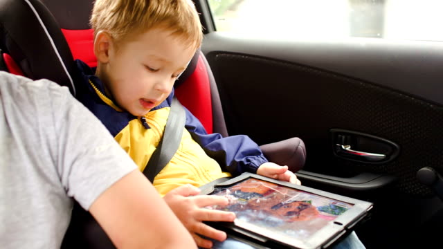 Happy boy playing game on pad during car travel video