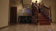 Happy boys running down staircase. video