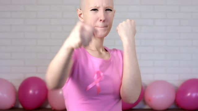 Happy breast cancer survivor woman fighting breast cancer making boxer's punches -breast cancer awareness concept video