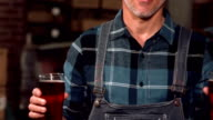 Happy brewery worker holding two pints video