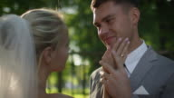 Happy bride and groom hold hands in a sunny park. video