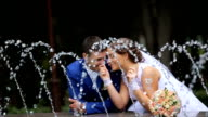 happy bride and groom standing near the fountain in the park video