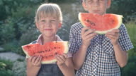 Happy Brother and Sister Eating Watermelon in Garden video