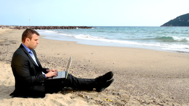 Happy businessman at the beach video