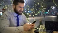 Happy businessman browsing smartphone, night, cafe, slider dolly shot video