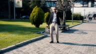 Happy businessman dancing along an urban walkway video