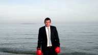 Happy businessman jumping with red boxing gloves video