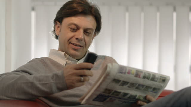 Happy businessman reading real estate ads on newspaper video