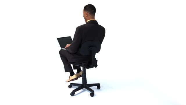 Happy businessman spinning in chair with laptop video