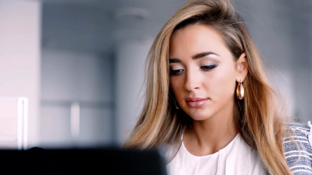 Happy businesswoman working on her laptop in the office video