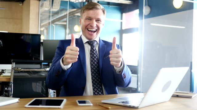 Happy bussinessman giving thumbs up to camera in his office video