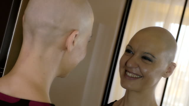 Happy cancer survivor after successful chemotherapy looking into the mirror video