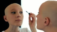Happy cancer survivor woman putting on make up, looking in the mirror video